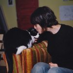 Animator Jo Dery gives her black and white cat Panda a kiss on the head.