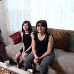 Three women of the Jassar family sit in the family room of their Chicago apartment