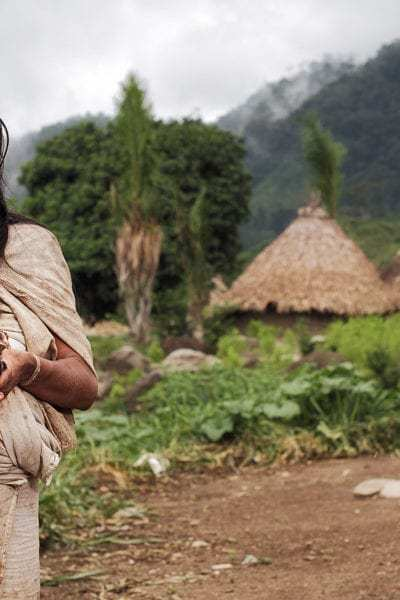 A woman of a Kogi (Kougi) community standing in the village holding a chick © | Alexander Reiser