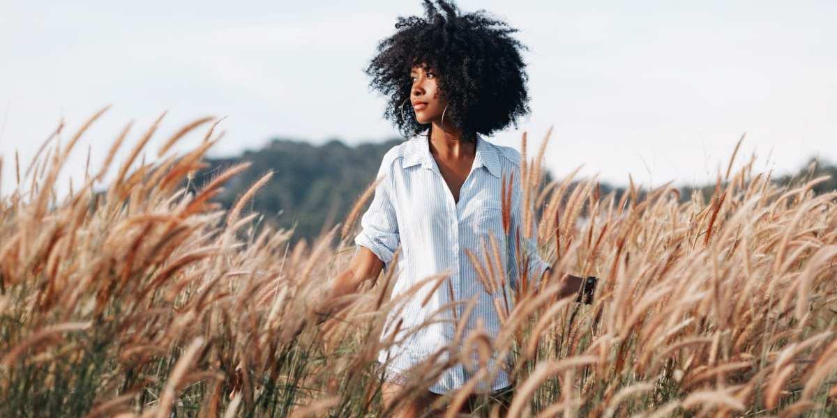 A young African American woman walks through a field at sunset ©   Zolotarevs/Shutterstock