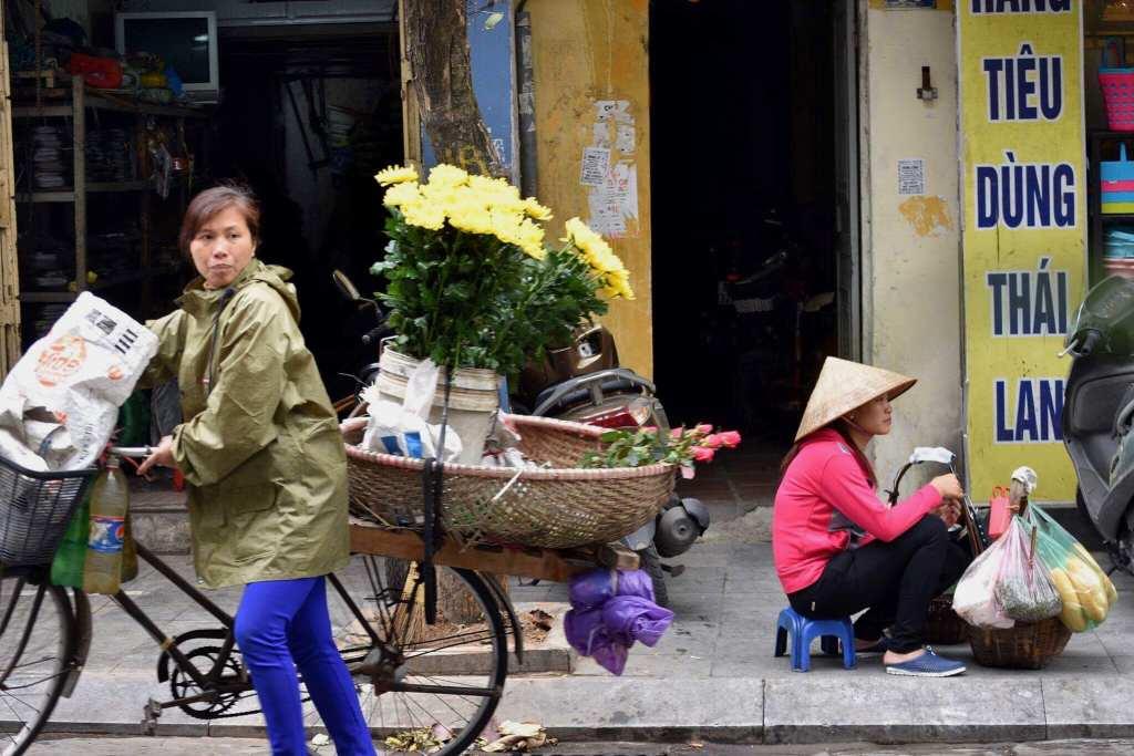 A local woman passes a sidewalk street vendor selling fresh food © | Nikki Vargas