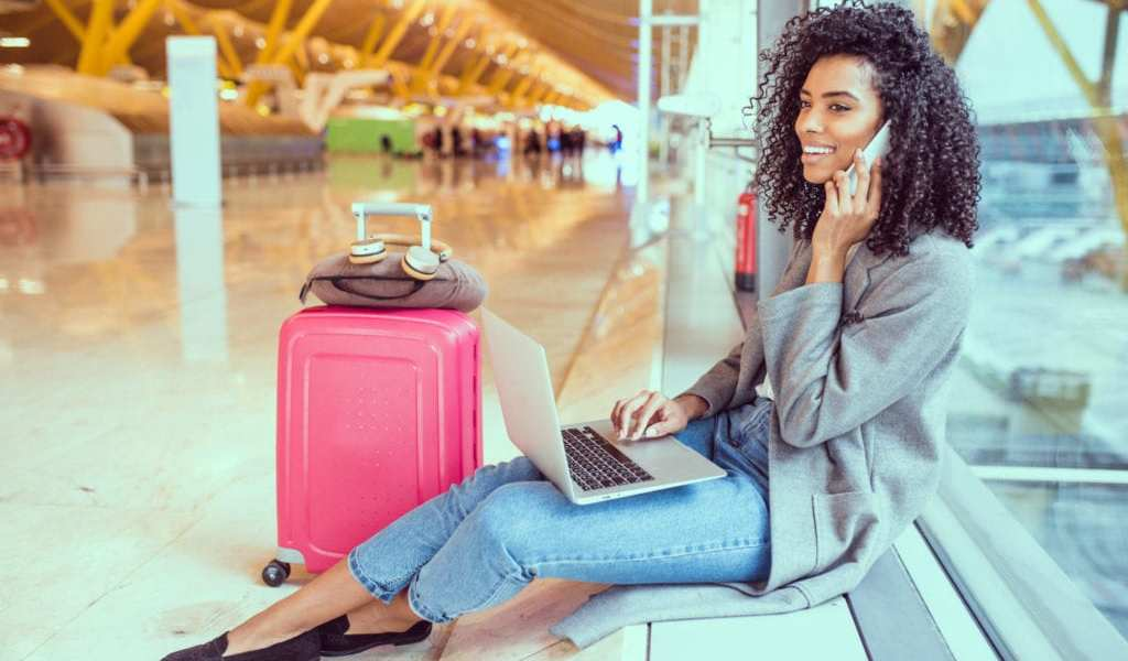 A young woman sits at the airport on her laptop | © David Prado Perucha/Shutterstock