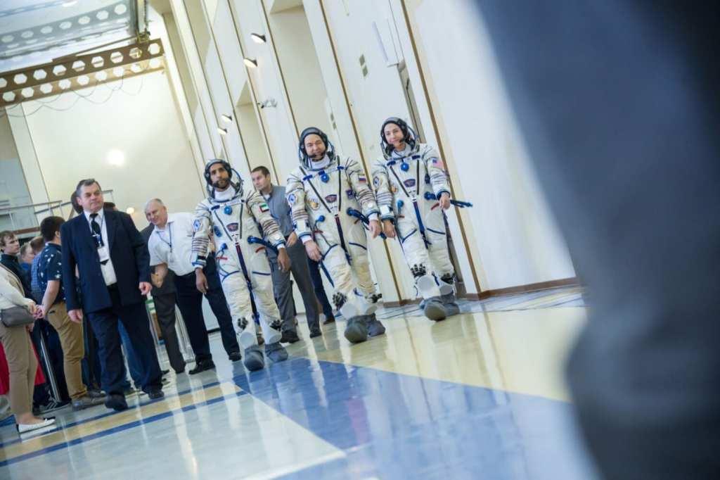 Hazzaa Ali Almansoori of the United Arab Emirates, left, Oleg Skripochka of Roscosmos, center, and Jessica Meir of NASA report for duty | © Mark Sowa/NASA