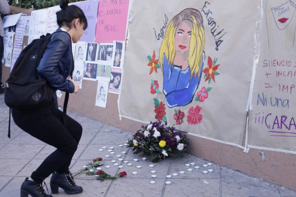 A woman leaves flowers in front of a memorial for Ingrid Escamilla | © Reuters