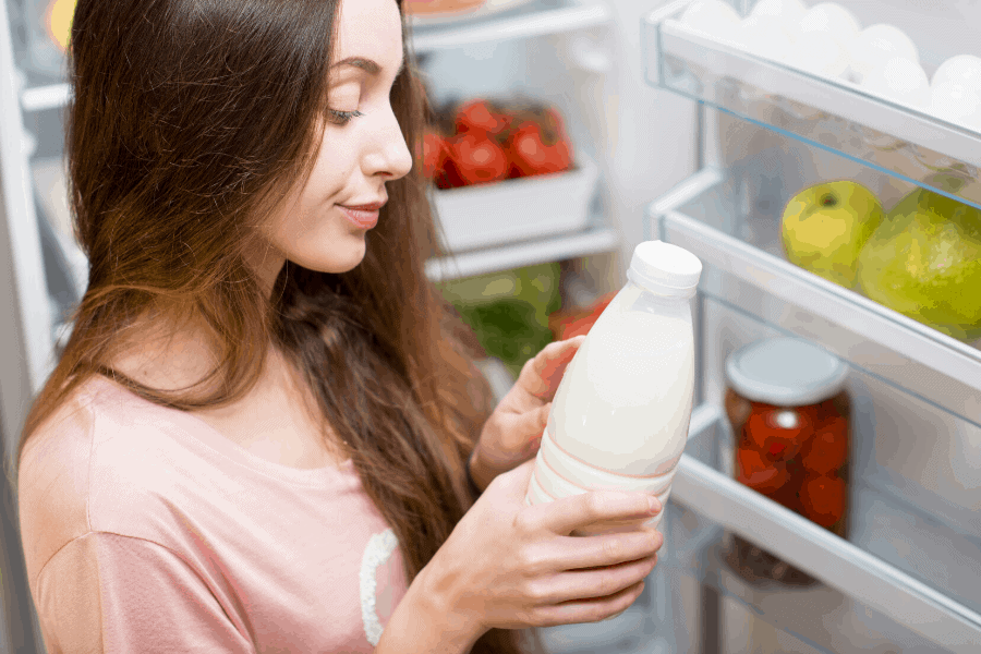 woman with brown hair checking expiration date on milk in front of refrigerator