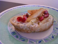 A picture of crostini with goat's cheese, pear shavings with ground fennel and pomegranate seeds