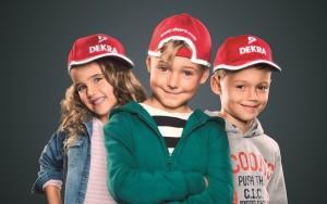 Knallrote Kinderkappen erhöhen die Sichtbarkeit für Schulanfänger. Foto: Dekra.