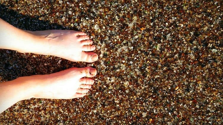 bare feet on sea glass beach