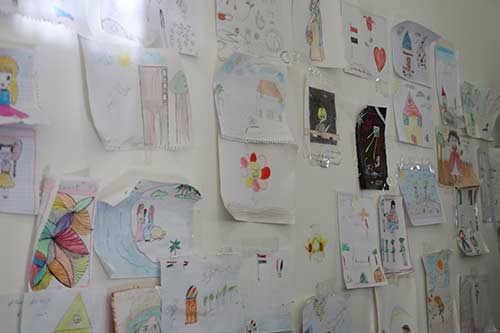 Drawings and messages adorn the wall of a women's shelter.