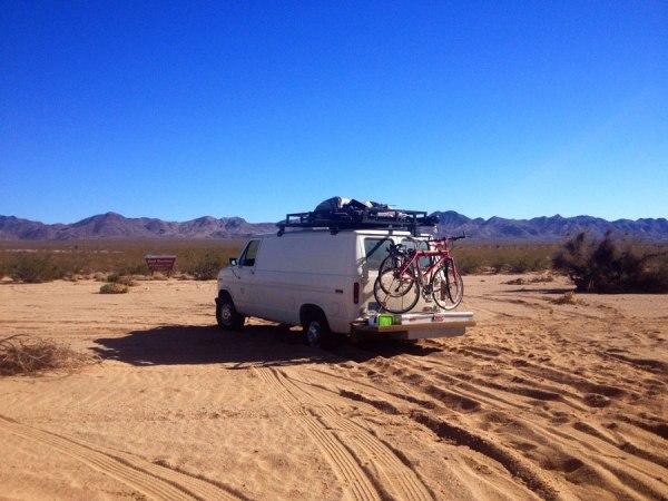 camper van with bikes in desert