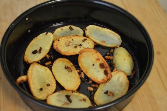 Ferdigstekte potetskiver legges i en kakeform.