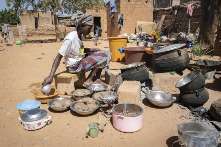 A displaced woman cooks food at a relative's house in Kaya, Burkina Faso.
