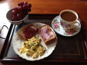 """Breakfast at Wimbledon""  — scrambled-up eggs with garden kale, basil and cilantro, added toast with jam, red grapes and dark roast coffee."