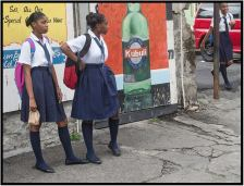 December 2: Schoolkids waiting for their ride home, photographed on Nov, 22 in the town of Roseau, Dominica. As an aside, the national Kubuli beer advertised on the billboard es muy bueno!