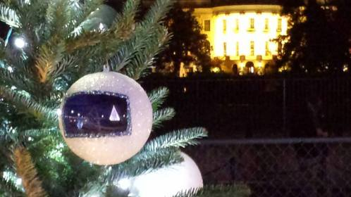 The National Christmas Tree reflected in the white ornament on the North Dakota Christmas Tree.