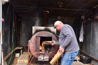 Ron Bowman adds wood to the fire under the maple sap vat.