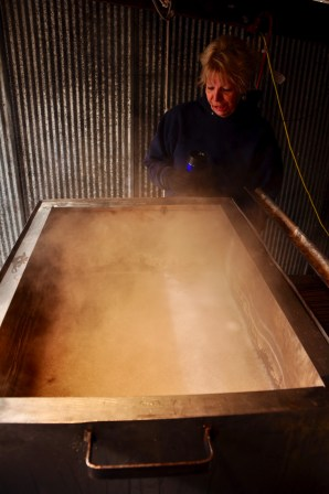 Marsha Bowman looks on at the vat boiling down the sap for maple syrup.