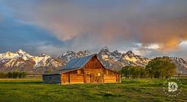 "June 23: ""The Moulton Barns on Mormon Row"": Rain clouds had just passed over me when the sun came up and lit up the barn, clouds and the peaks of the Tetons."