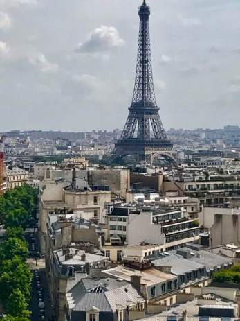 """June 6: The Eiffel Tower always amazes me as the inspiring visual centerpiece of the great city of Paris. I took this iPhone picture from the top of the Arc de Triomphe. Today is our last full day here. I ain't getting any younger, but I plan to return next year for the International Hemingway Conference. But as the French proverb he often quoted says, """"d'abord il faut durer."""""""
