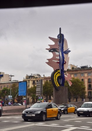 """This public art sculpture located in a roundabout is titled """"Face of Barcelona"""" and was designed by the American sculptor Roy Lichtenstein for the 1992 Olympics. It is said to be a tribute to Picasso, Dali and Miro. This gem of concrete and ceramic is 19.5 meters high and represents a woman's head with hair in the wind."""