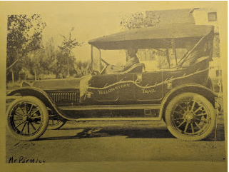 """The """"official"""" Yellowstone Trail automobile with Parmley at the wheel (date unknown). The Pacific Ocean is on the left and a yellow band encircles the car."""