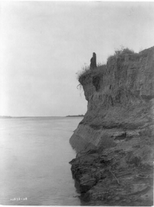 "Photograph by Edward S. Curtis, c. 1908. ""Mandan man wrapped in buffalo robe standing on cliff overlooking the Missouri River."" (From Wikimedia Commons.)"