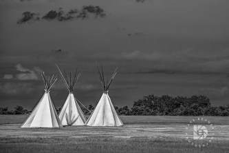 A black-and-white composition of these teepees depicts a nostalgic scene. A shadow reflection of the poles on the teepee side along with a dark stormy sky completed this scene.