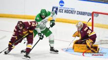 March 27, 2021 Minn. Duluth defenseman Connor Kelley (25) and North Dakota forward Judd Caulfield (28) battle for the puck in front of Minn. Duluth goaltender Zach Stejskal (35) during the championship game of the NCAA men's hockey Midwest Regional between the University of Minnesota - Duluth Bulldogs and the University of North Dakota Fighting Hawks at Scheels Arena, Fargo, ND. The game went to 5 overtimes and is the longest game ever played in NCAA tournament play. Minnesota Duluth won 3-2 and moves on to the Frozen Four. Photo by Russell Hons/CSM