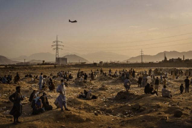 A military transport plane launches while Afghans who cannot get into the airport to evacuate, watch and wonder while stranded outside, in Kabul, Afghanistan on Aug. 23, 2021. (Marcus Yam/Marcus Yam / Los Angeles Times).