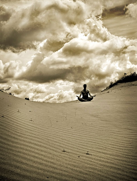 Sivatagban meditáló férfi, hömpölygő felhőkkel a háttérben