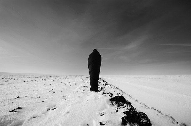 Fekete-fehér fotó egy alakról, aki háttal áll magában egy havas tájon