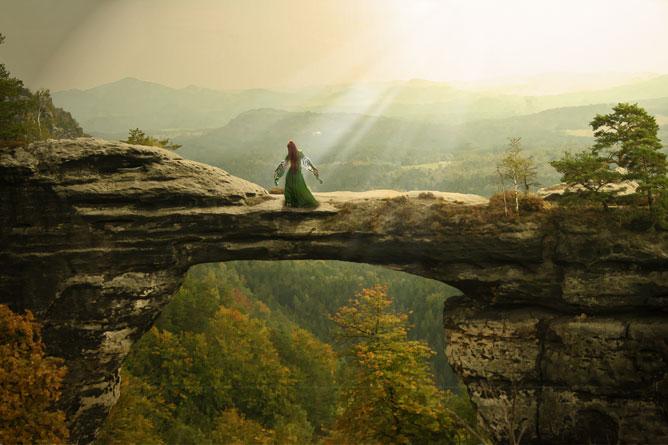 Ragyogó nypsütés; a hegy tetején, széttárt karokkal álló női alak.