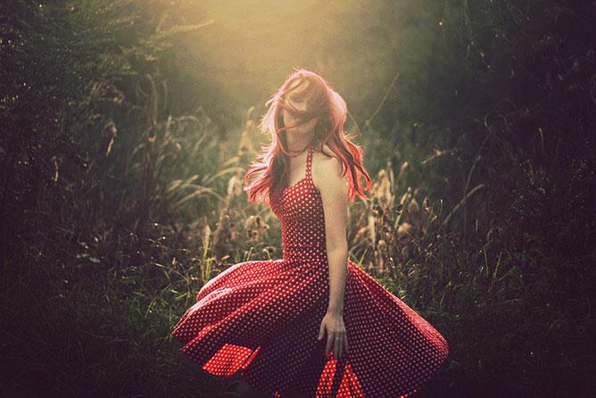 Piros pöttyös ruhás lány a réten.