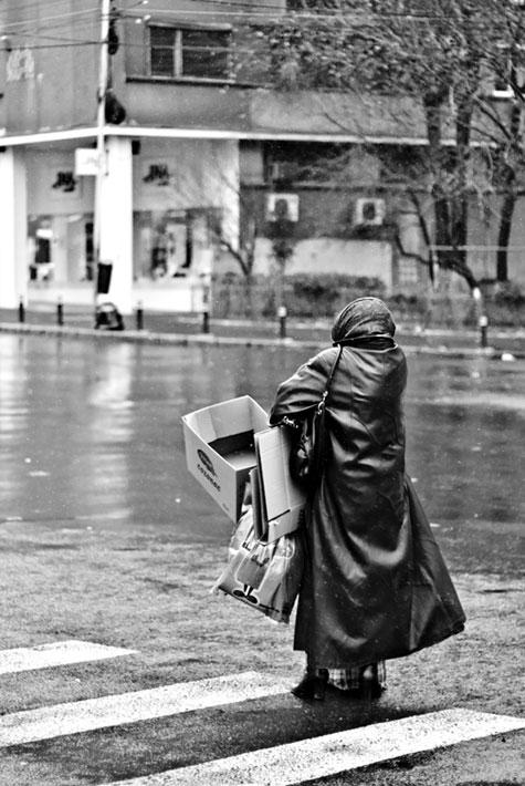 Hajléktalan öregasszony az utcán
