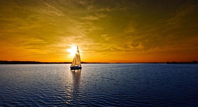 Vitorlás a naplementében a tengeren.