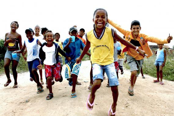 Um grupo de crianças corre em direção à câmera. Elas estão numa estrada de terra, no Semiárido brasileiro.