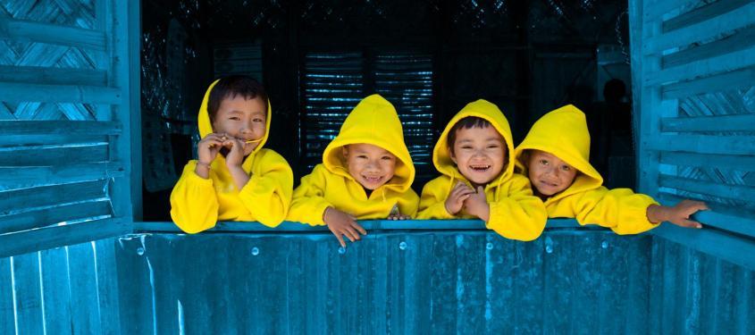 Four children look out an open window, Bangladesh