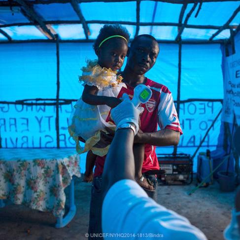Un hombre carga a una niña para una toma de temperatura en Sierra Leona