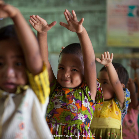 Unos niños de Bangladesh alzan sus brazos mientras practican un baile