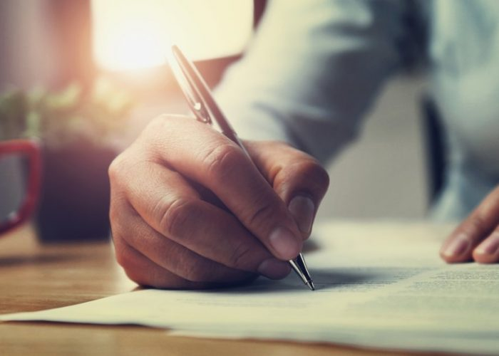 hand of woman holding pen with writing on paper report in office