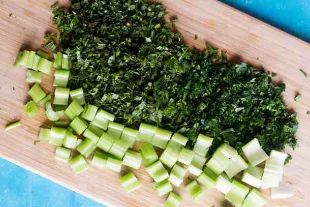 chop parsley, mint and celery on a chopping board.