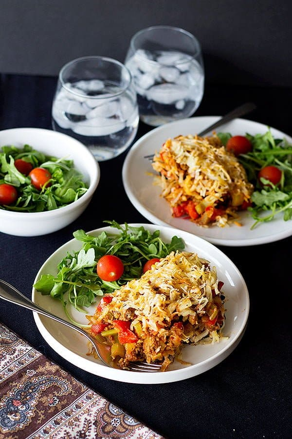 two plates of eggplant casserole with arugula and tomatoes.