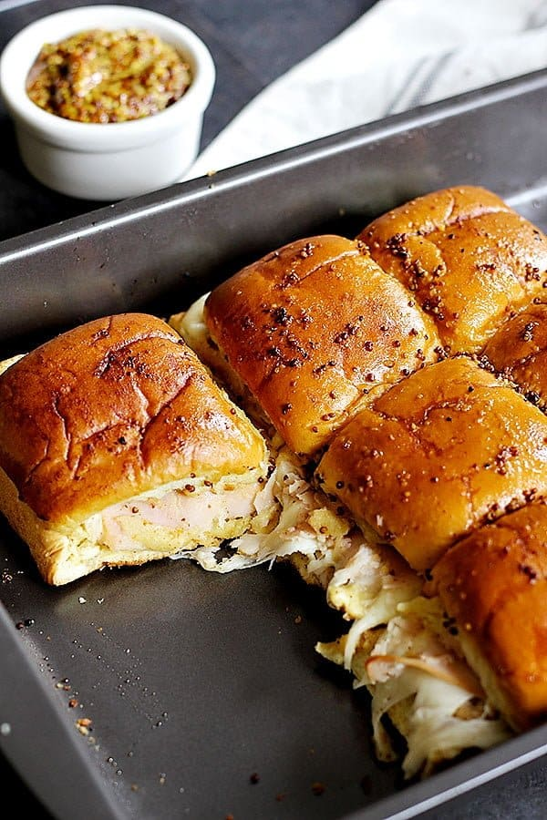 turkey sliders on hawaiian rolls with Swiss cheese and grainy mustard baked in the oven.
