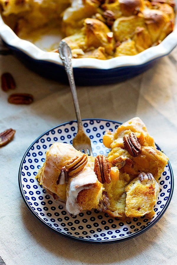 homemade bread pudding made with pumpkin and topped with coconut maple cream and pecans