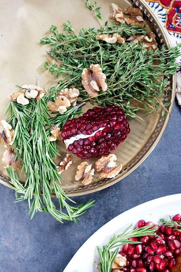 Use pomegranates and herbs to garnish the turkey.
