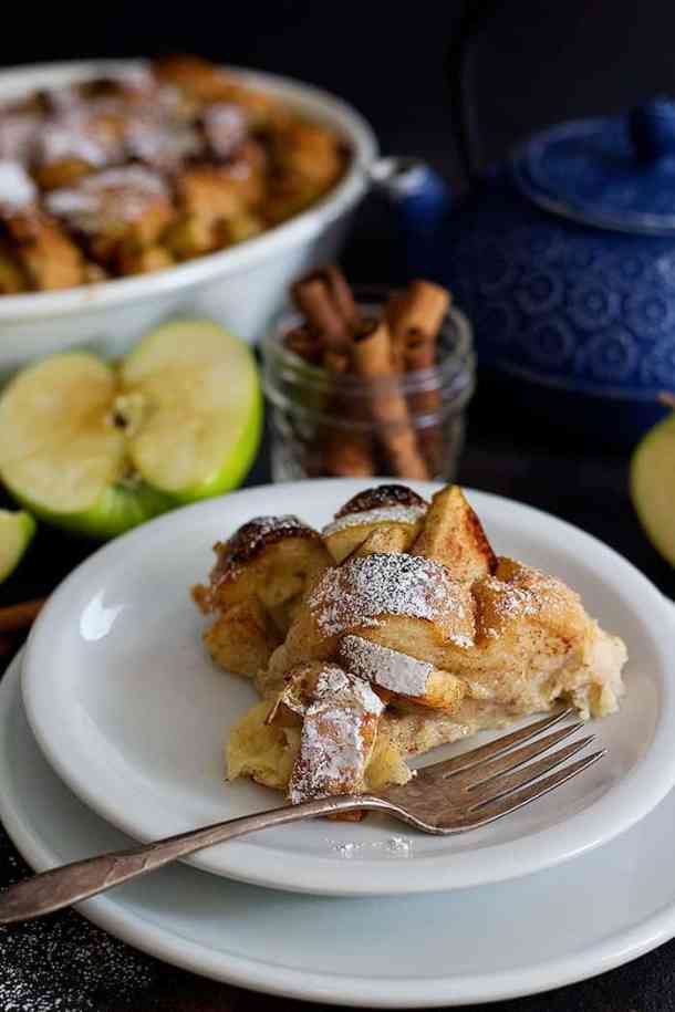 A slice of gooey apple Cinnamon breakfast bake on a white plate.