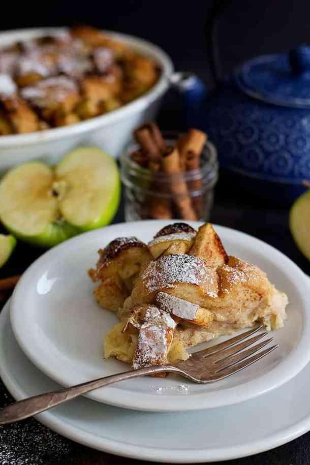 A slice of gooey apple Cinnamon breakfast bake on a white plate.
