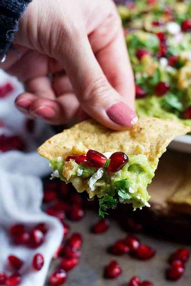 Pomegranate Guacamole on tortilla chips with cilantro.