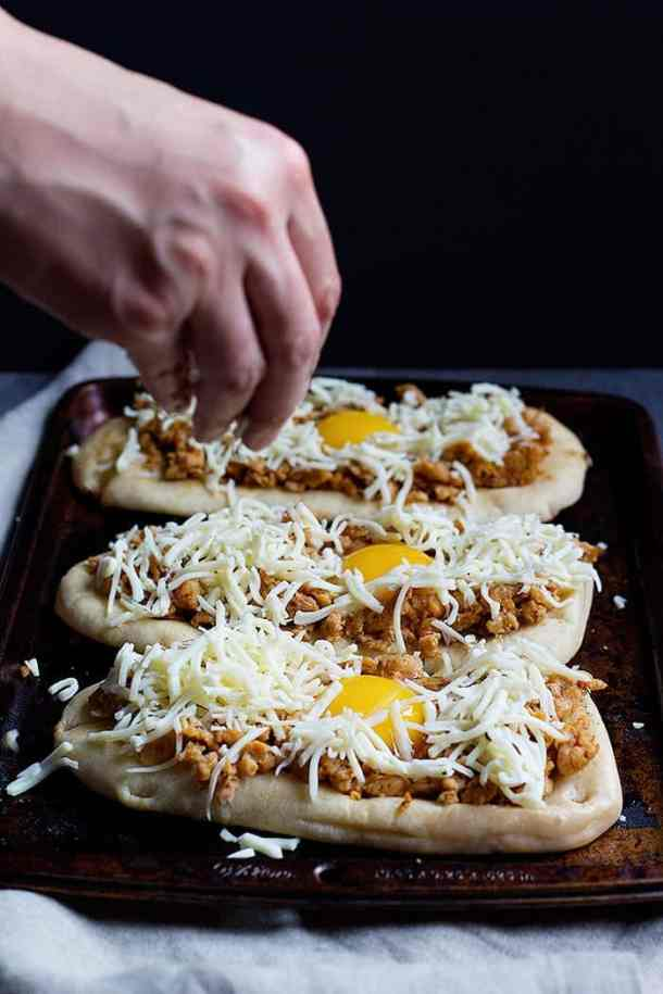 Top breakfast pizzas with sausage and shredded mozzarella cheese.