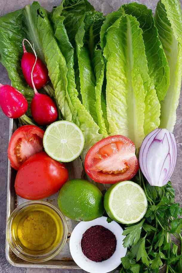 Lebanese salad ingredients are lettuce, radishes, tomatoes, lime, onion, sumac and parsley.